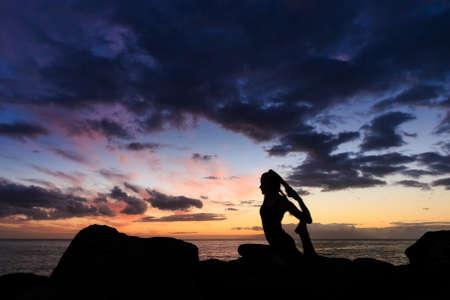 eka: Summer sunset yoga session on beautiful Playa Fanabe beach - tropical Tenerife island, Canary in Spain. Eka Pada Rajakapotasana - legged king pigeon pose Stock Photo