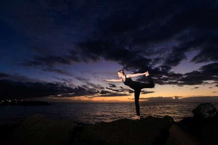 virabhadrasana: Summer sunset yoga session on beautiful Playa Fanabe beach - tropical Tenerife island, Canary in Spain. Warrior pose - Virabhadrasana Stock Photo