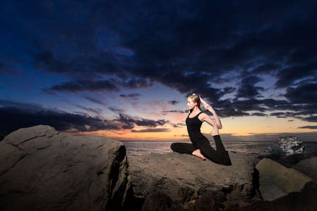 pada: Summer sunset yoga session on beautiful Playa Fanabe beach - tropical Tenerife island, Canary in Spain. Eka Pada Rajakapotasana - legged king pigeon pose Stock Photo