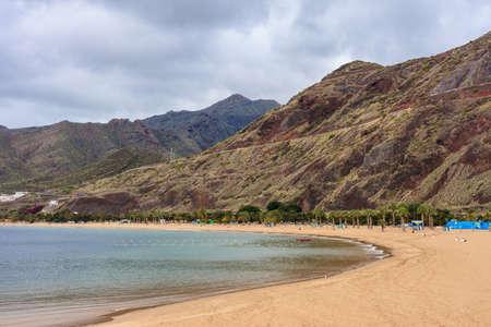 santa cruz de tenerife: Summer seascape on tropical island Tenerife, Canary in Spain. Playa de Las Teresitas beach with gold sand brought from Sahara desert view on capital city Santa Cruz De Tenerife.