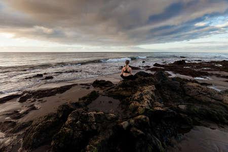 padma: Summer sunrise yoga session on beautiful Playa de La Tejita beach with view on atlantic ocean and Punta Roja rock - tropical Tenerife island, Canary in Spain. Meditation - lotus pose - padma asana