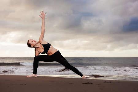 trikonasana: Summer sunrise yoga session on beautiful Playa de La Tejita beach with view on atlantic ocean and Punta Roja rock - tropical Tenerife island, Canary in Spain. Triangle pose - trikonasana Stock Photo