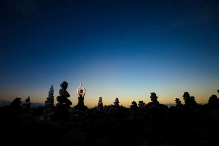 padma: Summer sunset yoga session on beautiful Playa del Duque beach with stone pile stacks silhouettes - tropical Tenerife island, Canary in Spain. Meditation - lotus pose - padma asana