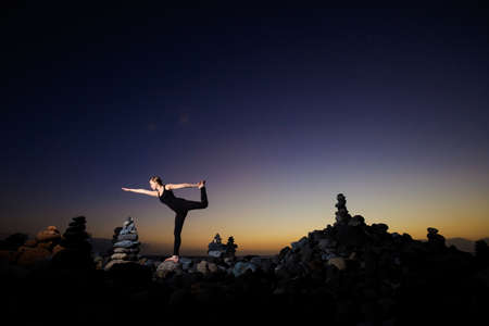 warrior pose: Summer sunset yoga session on beautiful Playa del Duque beach with stone pile stacks silhouettes - tropical Tenerife island, Canary in Spain. Warrior pose - Virabhadrasana