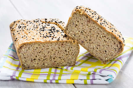 Homemade DIY natural vegan very healthy bread made of buckwheat, water, salt with black and white sesame, conopy seeds on a wooden table Imagens