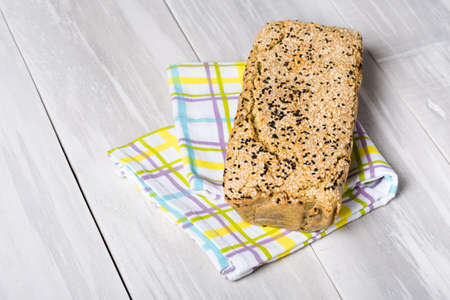 nigella seeds: Homemade DIY natural vegan very healthy bread made of buckwheat, water, salt with black and white sesame, conopy seeds on a wooden table Stock Photo