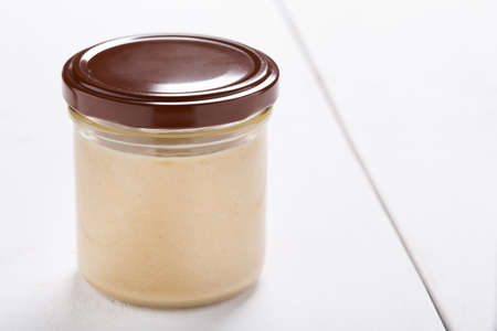 Homemade DIY natural vegan very healthy tahini paste made of sesame seeds in a glass jar on a wooden table