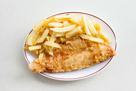haddock: Traditional english meal - deep fried fish, haddock with chips served in local restaurant in Hastings, England. Stock Photo