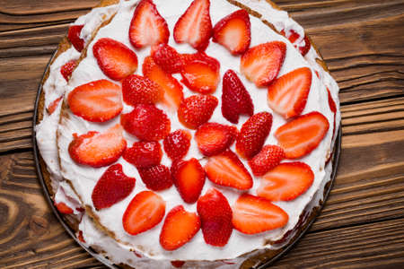 starch: Homemade DIY natural spring vegan layer cake. Sponge  made of chickepeas water, coconut, backwheat flour, potato and tapioka starch with coconut - wanilla filling and fresh strawberries on a wooden table