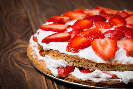 layer cake: Homemade DIY natural spring vegan layer cake. Sponge  made of chickepeas water, coconut, backwheat flour, potato and tapioka starch with coconut - wanilla filling and fresh strawberries on a wooden table