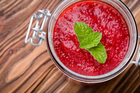 Homemade DIY natural healthy vegan strawberry jam made with chia seeds in glass jar on a wooden table. Raw food diet. Stock fotó