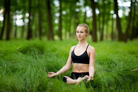 jnana: Nature yoga session in beautiful green polish woods, between trees. Meditation - jnana mudra in lotus pose. Healthy lifestyle concept Stock Photo