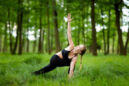 trikonasana: Nature yoga session in beautiful green polish woods, between trees. Twisted triangle pose, Parivrtta bikram Trikonasana