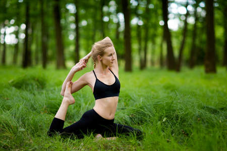 pada: Nature yoga session in beautiful green polish woods, between trees. One-Legged King Pigeon Pose, Eka Pada Rajakapotasana