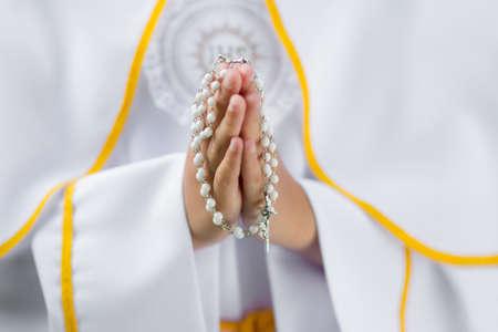Prima concept Santa Comunione - in primo piano il rosario sulle mani del bambino Archivio Fotografico