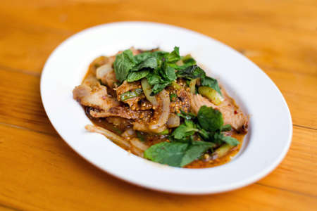 Thai fried Isaan style pork belly served with onion and mint. Traditional south east asian cuisine.