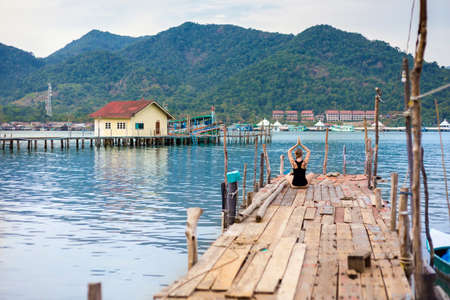 Summer yoga session on a pier - Koh Chang Bang Bao fisherman village, Meditation - lotus pose - padma asana. Activity in south east Asia