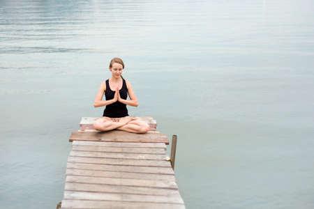 Summer yoga session on a pier - Koh Chang Bang Bao fisherman village, Meditation - lotus pose with namaste - padma asana. Activity in south east Asia