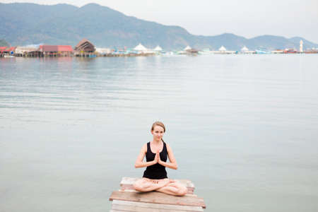 Summer yoga session on a pier - Koh Chang Bang Bao fisherman village, Meditation - lotus pose with namaste - padma asana. Activity in south east Asia