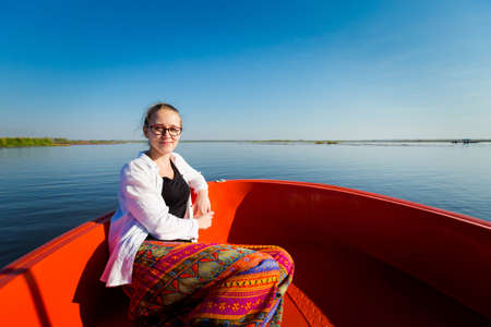 Beautiful women having a boat trip around Red Lotus Sea Kumphawapi full of pink flowers in Udon Thani in northern Thailand. Touristic places of south east Asia. Stock Photo