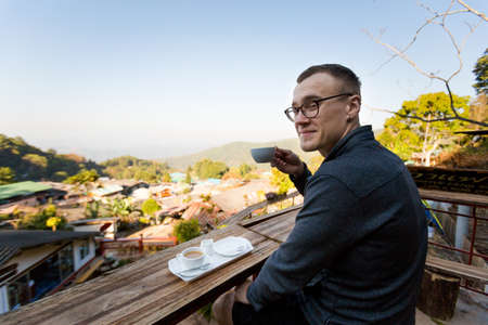 doi: Young caucasian man drinking coffee in paradise touristic Doi Pui village in Thailand close to Chiang Mai in northern Thailand. Beautiful landscape in souh east Asia.