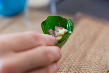 Popular thai snack Miang Kham made of betel leaf, ginger, onion, lime, coconut, peanuts, bird eye chilli and honey. Picture of traditional thai cuisine made of fresh ingredients taken during cooking class.