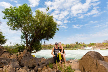 Young caucasian couple on Big Khone Phapheng waterfall - don phapheng, don khong, si phan don on four thousand islands in Laos. Landscape of nature in south east asia during summer.