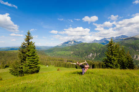 Summer yoga session in Tatra mountains. Warrior pose, Virabhadrasana. Beautiful panorama of Rusinowa Polana.