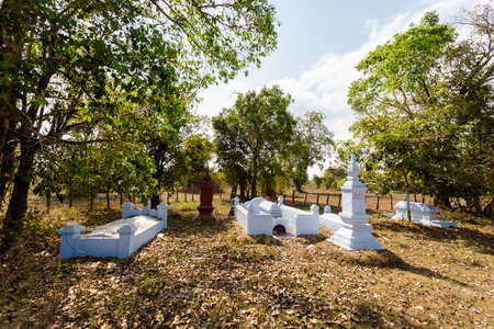 Landscape on Don Khone island in Laos. View with local cemetery taken in wild jungle on four thousands islands on Mekhong river in south east asia during summer.