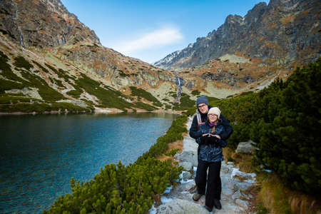 Couple on beautiful Velicka valley - in slovakian High Tatra mountains. Beautiful panorama with autumn and winter together - path from Sliezsky Dom to Polsky Hreben (Polski Grzebien)