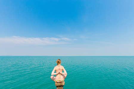 Nature yoga session on concrete Dai Mai pier - tropical koh Chang island  in Thailand. Meditation - namaste lotus pose - padma asana