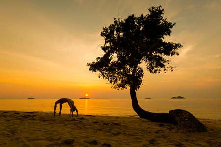 Summer sunset yoga session on beautiful Kai Bae  beach - tropical koh Chang island in Thailand. Chakra asana, wheel pose