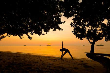 Summer sunset yoga session on beautiful Kai Bae  beach - tropical koh Chang island in Thailand. Triangle pose - trikonasana