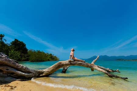 Summer yoga session on beautiful fallen tree on remote tropical island Ko Suwan near koh Chang in Thailand. Cobra Pose, Bhujangasana