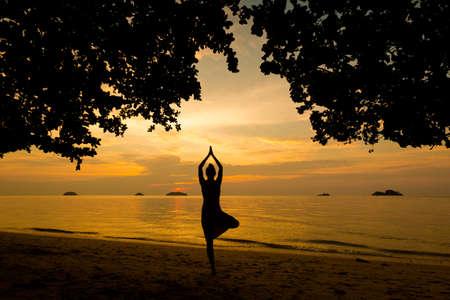 Summer sunset yoga session on beautiful Kai Bae  beach - tropical koh Chang island in Thailand. Vriksha-asana - tree pose.  Stock Photo