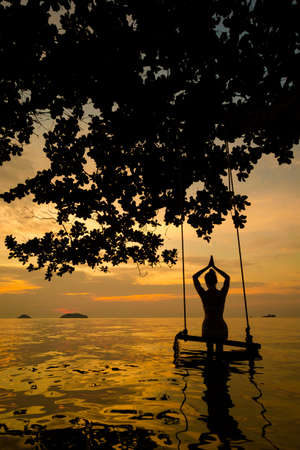 Summer sunset yoga session on beautiful Kai Bae  beach - tropical koh Chang island in Thailand. Namaste, Meditation - lotus pose - padma asana  Stock Photo