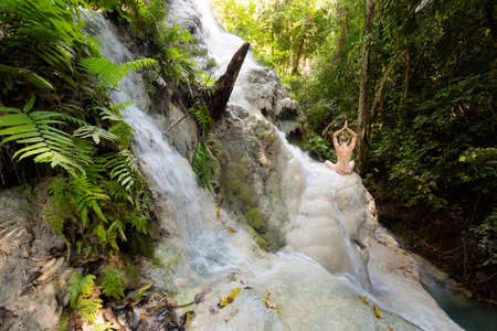 Tropical yoga session by beautiful Sticky Waterfall close to Chiang Mai in north Thailand. Namaste, Meditation - lotus pose - padma asana