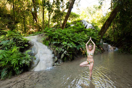 Tropical yoga session by beautiful Sticky Waterfall close to Chiang Mai in north Thailand. Vriksha asana - tree pose.