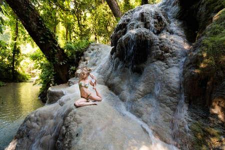 Tropical yoga session by beautiful Sticky Waterfall close to Chiang Mai in north Thailand. One-Legged King Pigeon Pose, Eka Pada Rajakapotasana Stock Photo