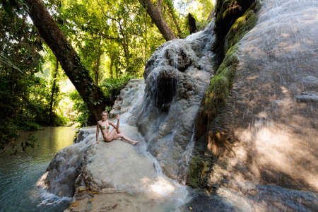 Tropical yoga session by beautiful Sticky Waterfall close to Chiang Mai in north Thailand. Ardha Matsyendrasana, half spinal twist  Stock Photo