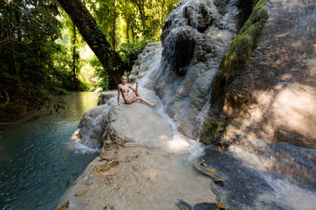 Tropical yoga session by beautiful Sticky Waterfall close to Chiang Mai in north Thailand. Ardha Matsyendrasana, half spinal twist