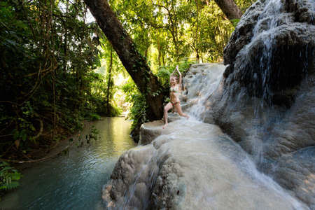 Tropical yoga session by beautiful Sticky Waterfall close to Chiang Mai in north Thailand. Warrior pose - Virabhadrasana  Stock Photo