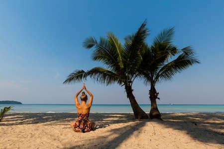 Tropical summer yoga session by beautiful Klong Chao beach, Koh Kood island in Thailand. Namaste, Meditation - lotus pose - padma asana Stock Photo