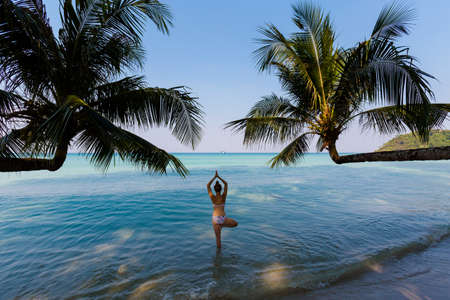 Tropical summer yoga session by beautiful Klong Chao beach, Koh Kood island in Thailand. Vriksha asana - tree pose.