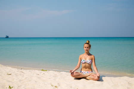 Tropical summer yoga session by beautiful Klong Chao beach, Koh Kood island in Thailand. Meditation - jnana mudra in lotus pose.