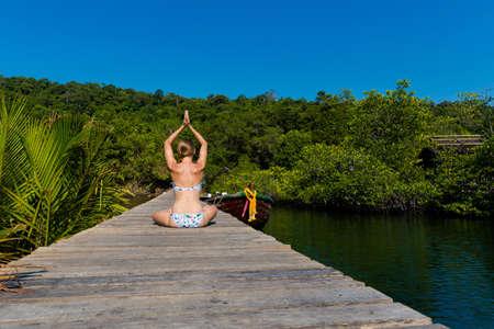 Tropical summer yoga session on Ao Noi beach pier, koh Kood island  in Thailand. Namaste, Meditation - lotus pose - padma asana Stock Photo