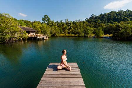 Tropical summer yoga session on Ao Noi beach pier, koh Kood island  in Thailand. Meditation - twisted lotus pose, padma asana  Stock Photo
