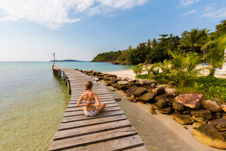 Tropical summer yoga session on Klong Mard pier, koh Kood island  in Thailand. Namaste, Meditation - lotus pose - padma asana