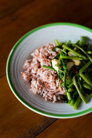 Thai fried morning glory with diced tofu served with red rice. Traditional south east asian cuisine.