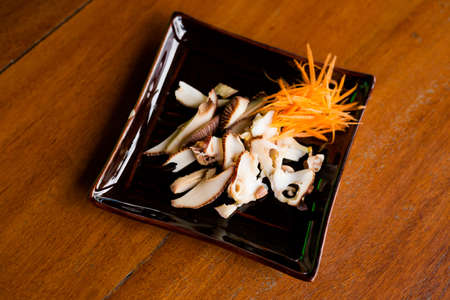Thai fried giant sea snail slices served with shreded carrot in local port restaurant. Traditional thai seafood cuisine made of fresh ingredients.